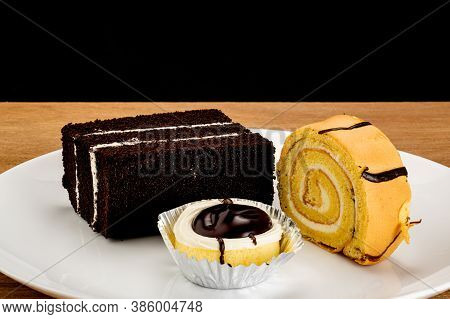 Three Kinds Of Dessert, Cake Roll, Cupcake, And Chocolate Butter Cake  In White Ceramic Plate On Woo