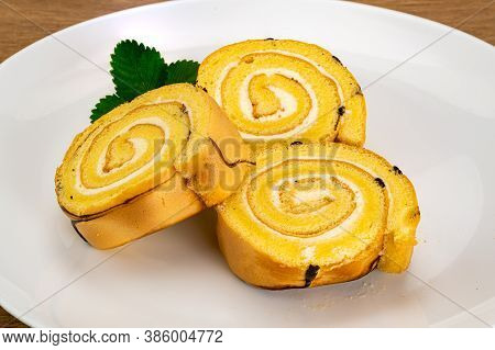 Pile Of Sliced Cake Roll In White Ceramic Plate On A Wooden Table.