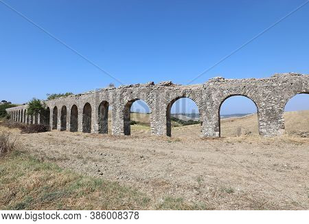 Ancient Aqueduct Made With Stones And Arches To Bring Water To The Roman City In Italy