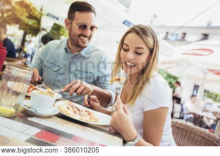 Photo Of Young Couple Enjoying In Pizza, Having Fun Together.