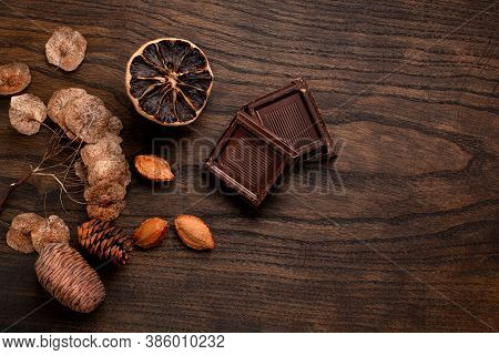 Composition Of Chocolate Two Pieces On A Wooden Background, Dried Lemon, Raisins, Plums, Pears, Waln
