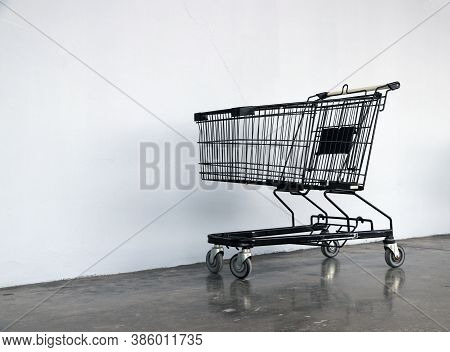 Black Shopping Cart On The Floor And White Background. Trolley Is A Cart Supplied By A Shop, Especia