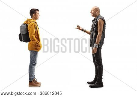 Full length profile shot of a punk rocker talking to a teenager boy isolated on white background