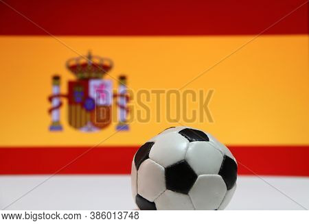 Small Football On The White Floor And Spanish Nation Flag Background. The Concept Of Sport, Spain Is