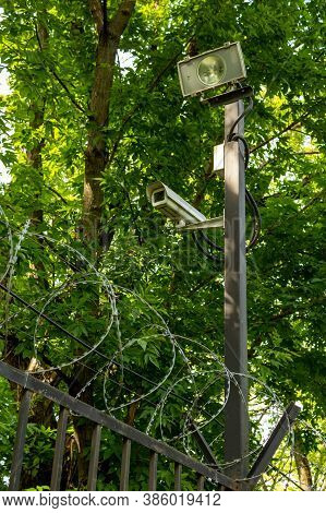 A Fence With Barbed Wire Protects The Territory Of The Military Base. Surveillance Cameras To Protec