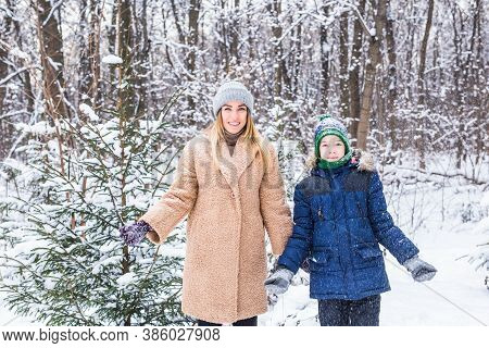 Parenting, Fun And Season Concept - Happy Mother And Son Having Fun And Playing With Snow In Winter