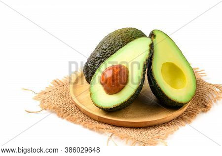 Avocado Half On Wood Plate Isolated On White Background. Ripe Fresh Green Avocado