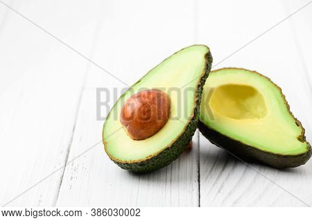 Avocado Half Isolated On White Wood Background. Ripe Fresh Green Avocado