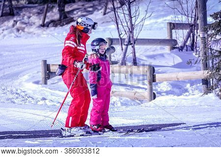 Lalpe Dhuez, France 02.01.2019 Professional Ski Instructor Is Teaching A Child To Ski On A Sunny Day