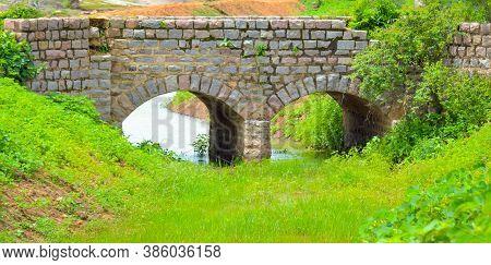 Old Stone Single Arch Bridge, Latvia. Famous Ancient Stone Arch Single Track Road Bridge In The Fore