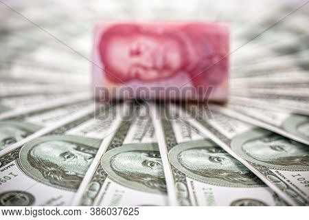 100 Dollar Banknotes With A Hundred Yuan Note (renminbi), Concept Of Devaluation Of The American Cur