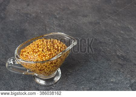 French Mustard In A Glass Sauceboat On A Black Background. Dijon Mustard.