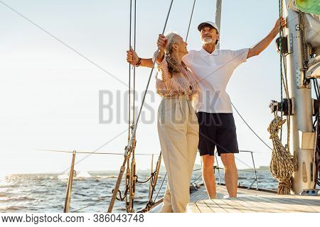 Elderly People Standing On Private Sailboat And Holding Ropes