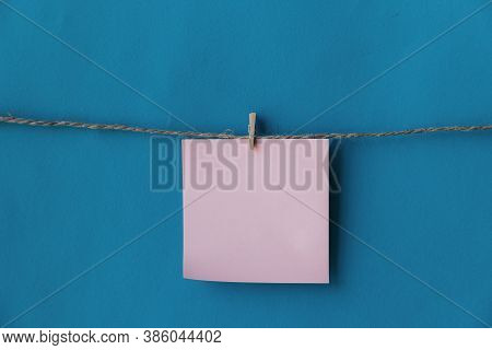 One Pink Sheet Of Paper With Place For Text Hanging On Rope Isolated Blue Background. To Do List. Pi