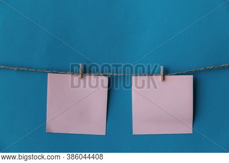 Two Pink Sheets Of Paper With Place For Text Hanging On Rope Isolated Blue Background. To Do List. P