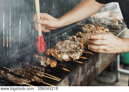 Hand Of Young Man Lubricates The Meat With A Sauce Brush On Long Rectangular Barbecue With Smoke On