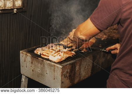 Hand Of Young Man Grilling Some Meat And Fish On Long Rectangular Barbecue With Smoke On The Street