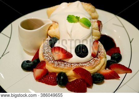 Closeup A Plate Of Souffle Pancakes With Fresh Mix Berries And  Mascarpone Cream