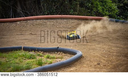 Yellow Electric Rc Buggy Racing On An Offroad Outdoor Track