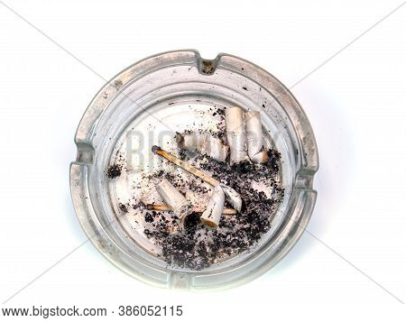 Glass Ashtray With Cigarette Butts On A White Background. The Harm Of Smoking. Ashtray Made Of Trans