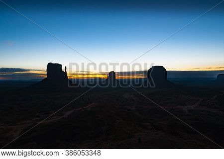 Rock Outcrops Of Monument Valley Silhouetted By Sunset Creating Contrasts Between The Structures And