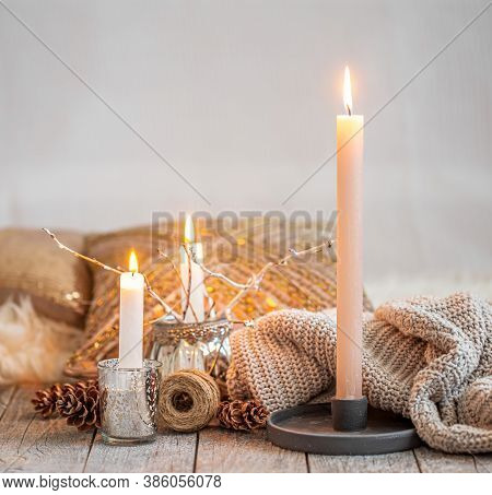 Cozy Home Interior, Burning Candles, Warm Sweater On A Wooden Table.seasonal Autumn-winter Concept O