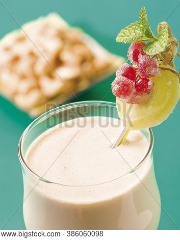 A Glass Of Healthy Cashew Nut Smoothie Woth Decoration On Blue Green Background.