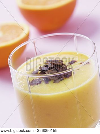 Closeup Of An Orange Smoothie Garnished With Chocolate Shavings.