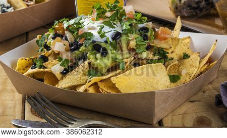 Mexican Take Away Food: Nachos With Guacamole, Frijoles, Tomato And Coriander.