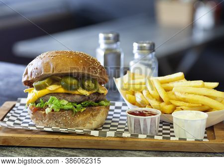 Hot Spicy Jalapeno Burger With Pepper Slices, Nachos And Cheese On A Tray At A Fast Food Restaurant.