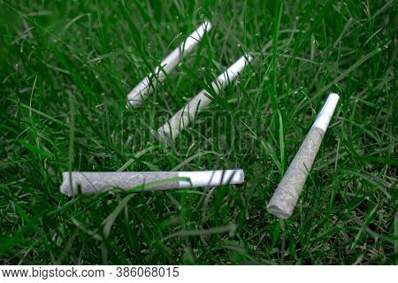 Pre-rolls Cannabis Joints Marijuana Weed On A Fresh Lawn Grass Surface.