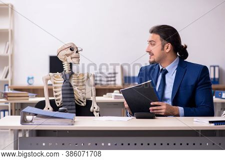 Young male employee with skeletons in the office