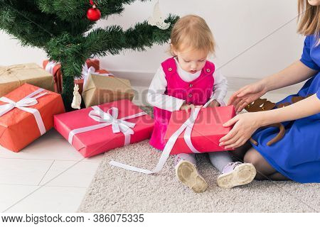 Smiling Mother Open Christmas Presents With Baby Daughter In Room At Background. Winter Season. Moth