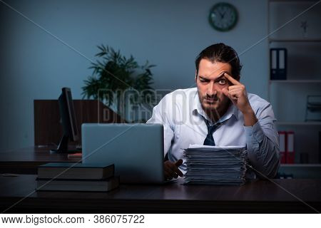 Young male employee working in the office night time