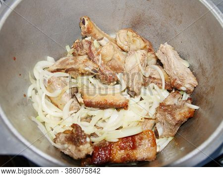 Pork Ribs Fried With Onions In A Cauldron.
