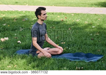Young Man In Sportswear Doing Yoga In The Park. Practice Asana Outdoors. Exercising On Green Grass W