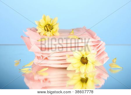Panty liners in individual packing and yellow flowers on blue background close-up