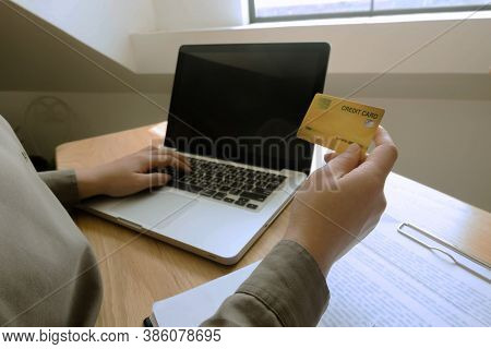 Woman Holding Credit Card And Using Laptop For Shopping Online.