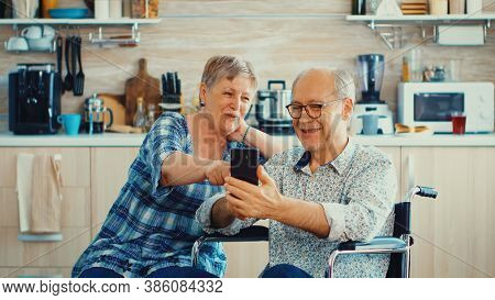 Smiling Senior Woman And Her Disabled Husband In Wheelchair Using Smartphone In Kitchen. Paralysied