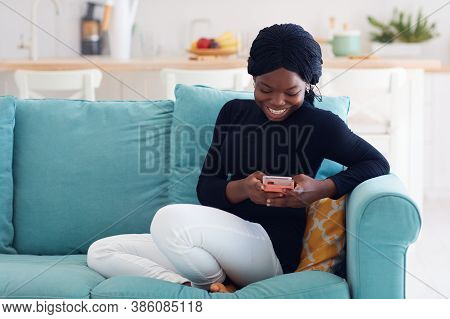 Smiling African American Woman Texting On The Phone At Home