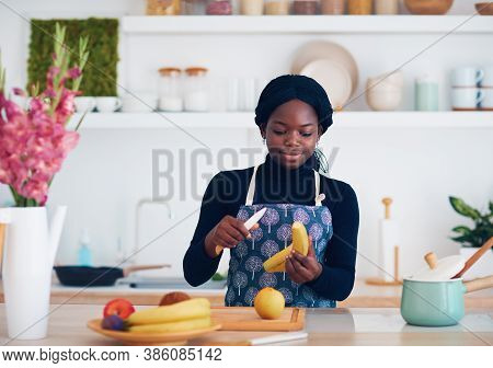 Young African American Woman Is Chopping Fruits At The Modern Kitchen