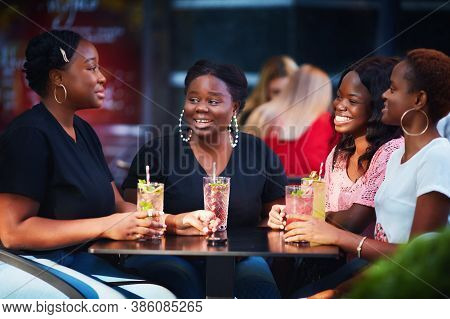 Happy Friends, African American Women Sitting Together At The Outdoor Restaurant At Summer Day