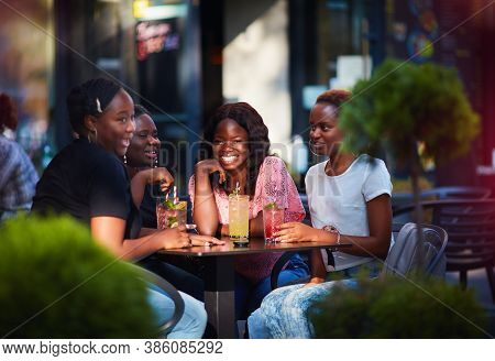 Happy African American Women, Friends Sitting Together At The Outdoor Restaurant At Summer Day