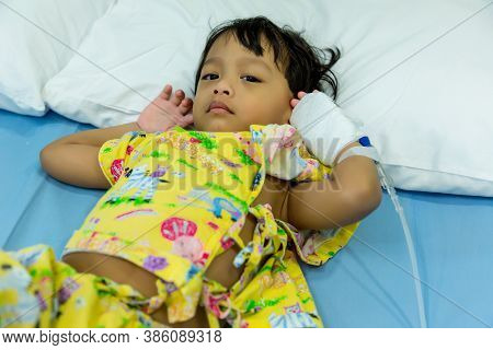 A Little Boy Attaching Intravenous Tube To Patient\'s Hand In Hospital Bed. Baby Sick And Sleeping O