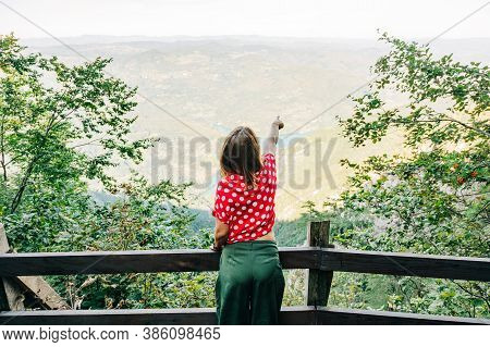 Young Female Nature Explorer Enjoying The View From Mountain Viewpoint