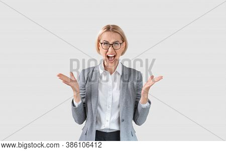 Attractive Female Entrepreneur In Formal Wear Screaming In Anger On Light Background. Company Employ