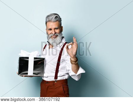 Bearded Old Man In A White Shirt, Brown Pants And Suspenders, A Bracelet. He Holds A Silver Gift Box
