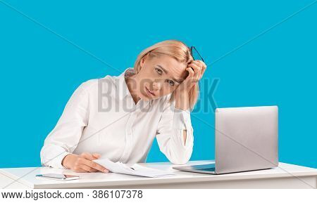 Attractive Businesswoman Tired Of Computer Work Sitting At Her Desk Over Blue Studio Background. Exh