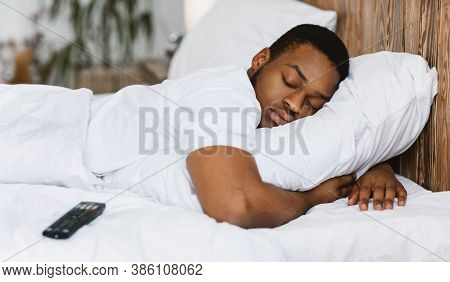 Fast Asleep Black Man Sleeping Embracing Pillow Resting In Bed At Home, Lying Near Remote Control Ti