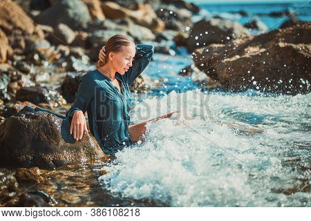 Woman In Blue Wet Dress Sitting In Crystal Sea Water. Meditation And Time For Relax. Summer Time And